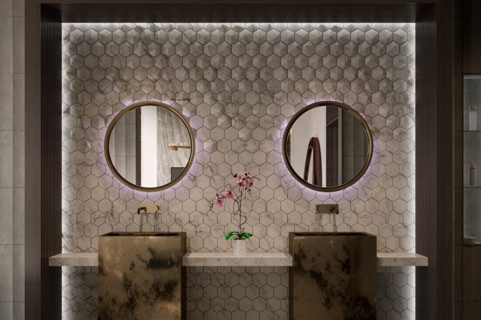 His and hers sinks against a detailed, grooved marble panel