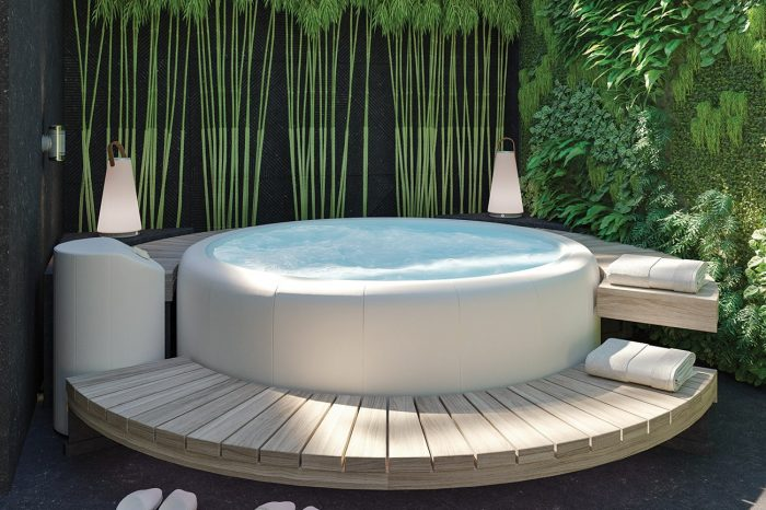 Jacuzzi with wooden decking and living green wall behind
