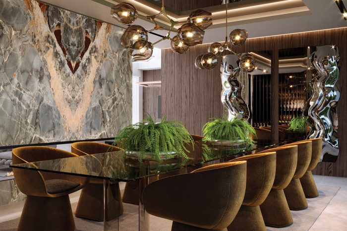 Formal Dining area. The onyx wall, floating over a natural fire, the walnut panelling and the subtle lighting bring warmth (both literally & metaphorically) to this opulent space.