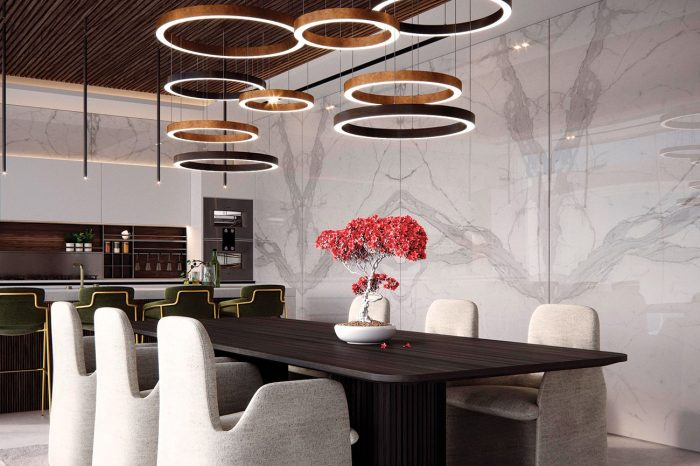 A Kitchen that looks like a dining room you can cook in, its large circular Henge lamps overlooking a dark wood table and light velvet chairs.