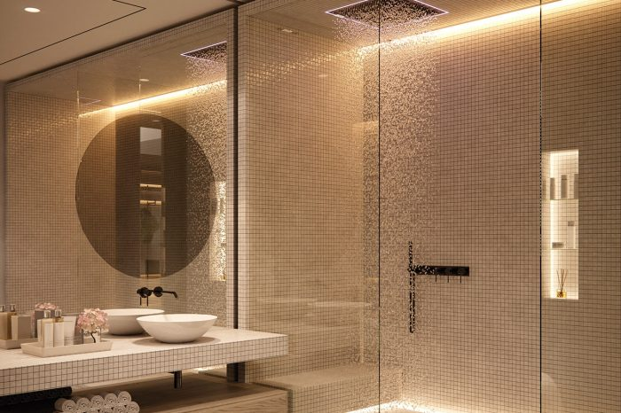 The large shower area with a bench and a back lit inset space for all shower items